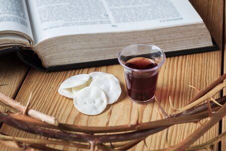 Heilige Kommunion, eine Tasse Wein und Brot mit einem Jesus-Kronendorn und der Bibel.