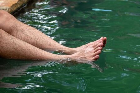 Male Tourist Relaxing His Happy Legs in the Hotspring Water Pond.
