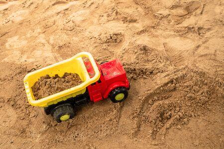 Children Toy Truck on the Sand Children Playground.