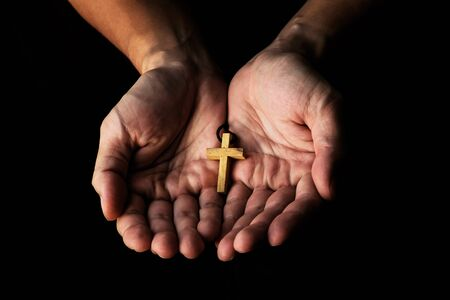 Man Giving Simple Wood Cross Sign. Concept of Evangelism Jesus Christ to the Others. Low Key Picture. 写真素材