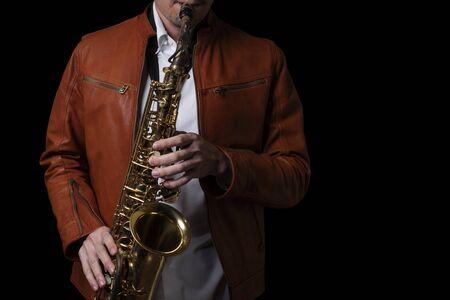 Performance masculine de joueur de saxophone de jazz sur la scène. Fond noir isolé. Banque d'images