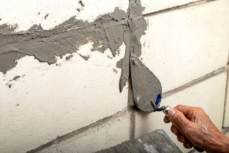 Skillful Old Man Plasterer Plastering Cement on the Old Brick Wall. Standard-Bild
