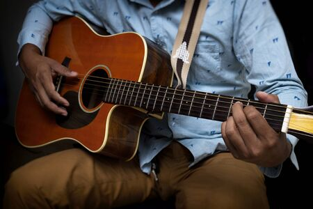 Male Guitar Musician Playing His Acoustic Guitar iSolated Black Background.