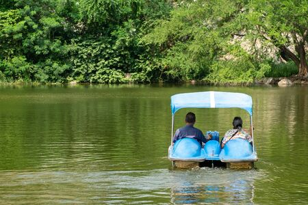 Cute Old Lover Couple playing a Water Bike in the Nature Lake.