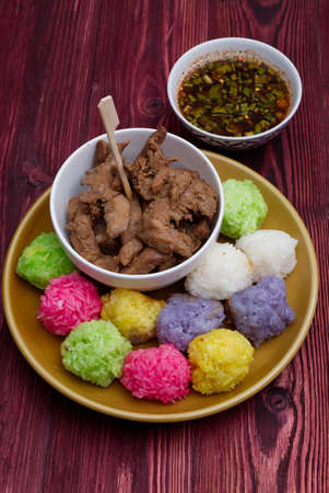 Various Colourful Sticky Rice with Fried Chicken meal on the Wood Table.