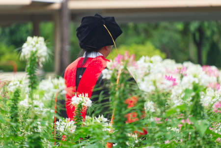 Doctor of Philosophy Graduate Elder Female Taking a Photo in the Beautiful Flower Garden 스톡 콘텐츠
