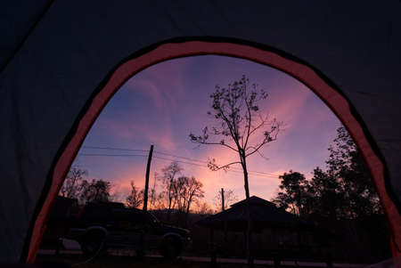 Beautiful Sunrise Morning from iNside of Tent. Camping with SUV Car in Front and Forrest.