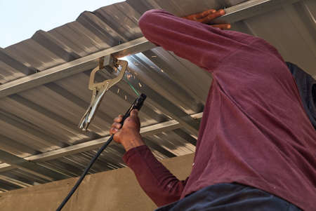 Skillful craftsman welding roof top metal bar in construction site.