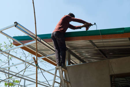 Unsafe Male Roofer Workman Using Electric Screwdriver Install Tile on Roof of New House in the Construction Site with no Protection.