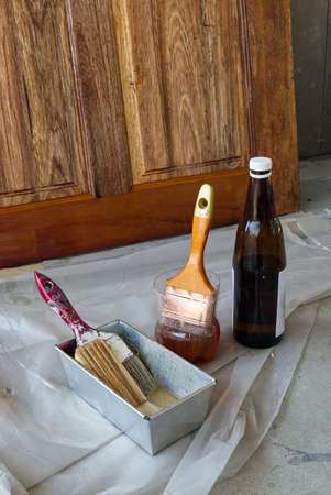 Paint Brush in the Plastic Jar contained Lacquer Prepared for Wooden Door Lacquering.