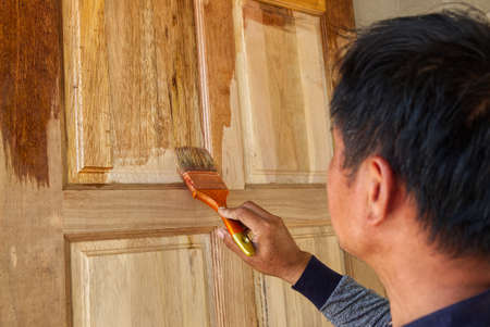 Painter Covering Lacquer Vanish on the Wooden Door in the Construction Work Site.