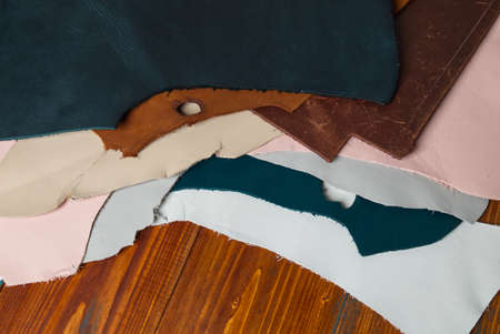 Various Kind and Color Genuine Leather Scraps on the Wood Table