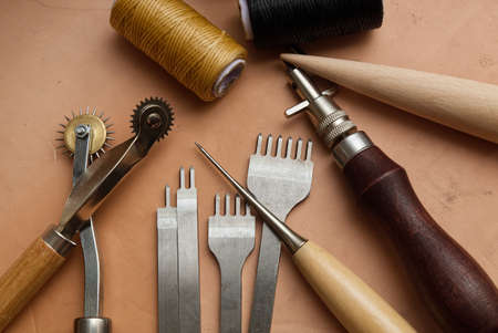 Leather Crafting Tools on the Genuine Leather on the Table, Handicraftsman Equipment for DIY Leather Works. 版權商用圖片