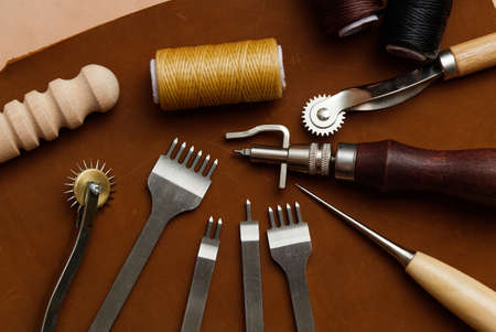 Leather Crafting Tools on the Genuine Leather on the Table, Handicraftsman Equipment for DIY Leather Works. Foto de archivo