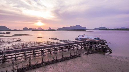 beautiful sunrise in fishing village in andaman sea .Cultured mussels near the pier of fishing village can see when low tide