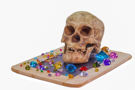 you can not take anything with you when you die.head skull on diamonds beside orb in white background. Stock Photo