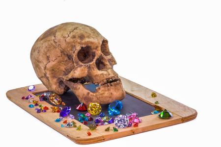head skull on diamonds beside orb in white background. Stock Photo