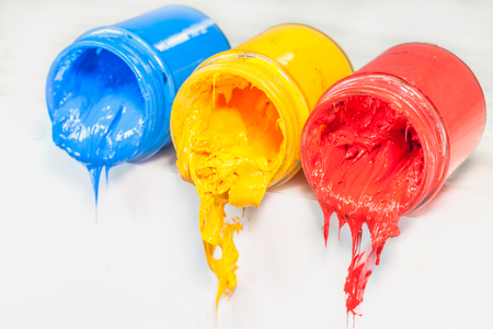 yellow blue and red colors of Plastisol ink on white table. Plastisol ink for print tee shirt and any fabric useful in tee shirt factory. yellow blue and red colors are primary color.