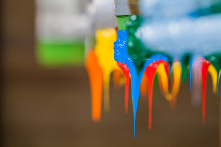 colorful of plastisol ink stick on printer handle start flowing down 免版税图像