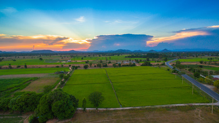 aerial view scenery sunset on new route pass in the rice field. under construction new motorway connect to Myanmar.