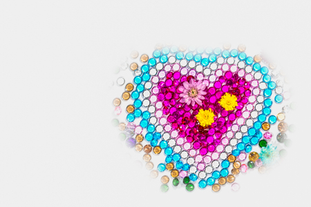 flowers and colorful polished gemstones in heart shape on white background. heart of love design with colorful gemstone for valentine day
