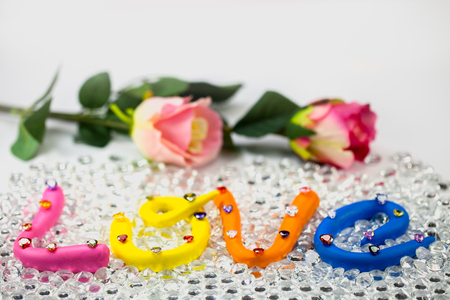 L in pink color O in yellow color V in orange and E in blue color. the word love in colorful alphabet decorate with diamonds for valentine day. Stok Fotoğraf