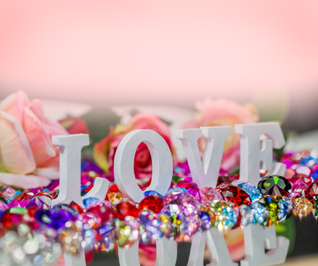 The word love is located on the area of colorful diamonds and roses, the word love is love for Valentines Day. Stock Photo