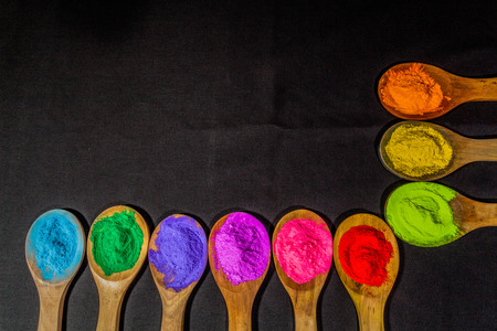 a row of colorful powder colors on wooden spoon in black background  with copy space Stock Photo