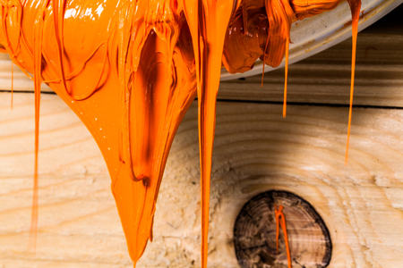 orange color of plastisol ink flowed out of the barrel. plastisol ink is specially for print on tee shirts and any fabric. the ink useful in tee shirt factory garment and industry for export Standard-Bild