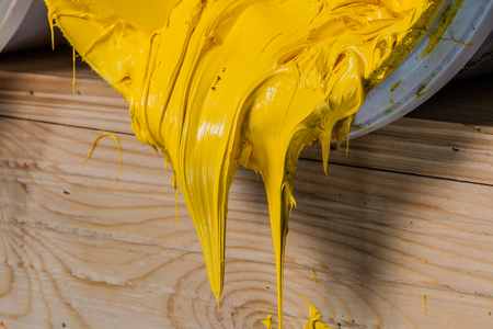 yellow color of plastisol ink flowed out of the barrel. plastisol ink is specially for print on tee shirts and any fabric. the ink useful in tee shirt factory garment and industry for export