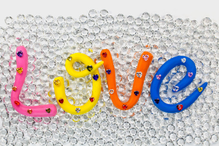 L in pink color O in yellow color V in orange and E in blue color. the word love in colorful alphabet decorate with diamonds for valentine day. Stock Photo