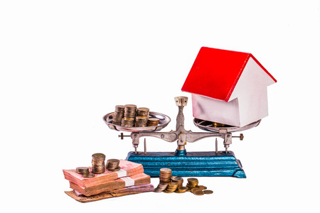compare salary to buy home different kinds money on scale in white background   copy space Reklamní fotografie
