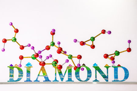 atom of diamond above glitter diamond letter on isolated background with copy space