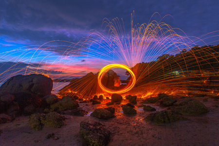 reflection of spark fire swirl from steel wool with long exposure speed motion abstract at sunrise in the sea