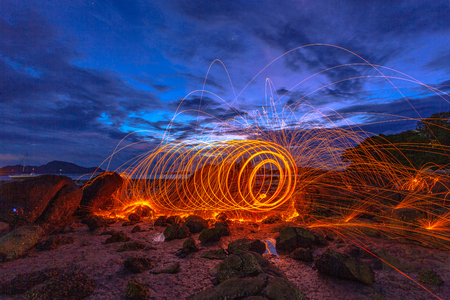 cool burning steel wool fire work photo experiments on the rock at sunrise. 写真素材