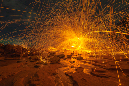 cool burning steel wool art fire work photo experiments on the beach at sunset Standard-Bild