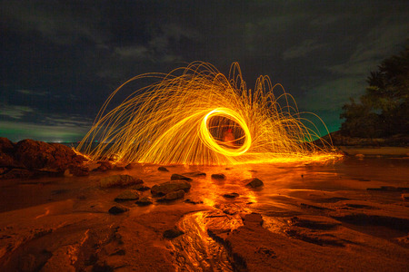 cool burning steel wool art fire work photo experiments on the beach at sunset Reklamní fotografie