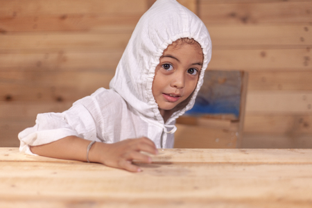 a cute long haired boy wearing a white shirt with a hood in wooden background