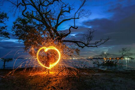 burning steel wool under mangrove tree in heart shape in twilight at Klong Mudong Phuket Thailand.