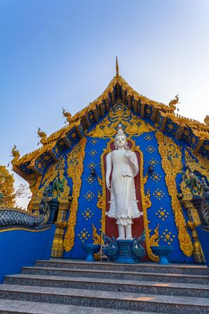 white standing buddha on the back of church in Rong Suea Ten temple Chiang Rai Thailand.