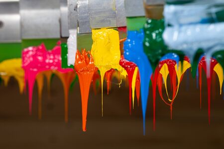 several dripping colors ink on handle printers in tee shirt factory hang on the storage Imagens