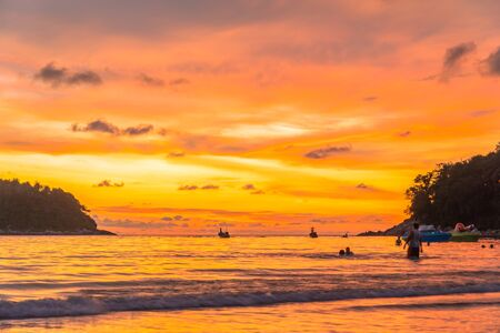 stunning sunset in channel between islands. Koh Pu or crab island is in  the middle between Kata beach and Karon beach tourists playing blow plat in sunset at Kata beach