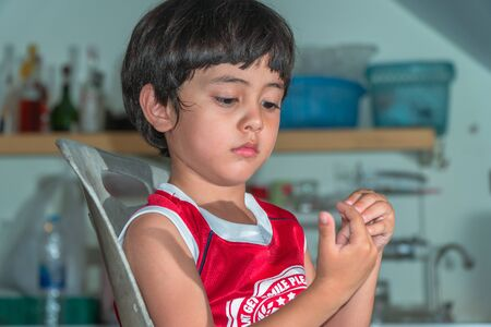 A boy wear red shirt sitting in the kitchen during waiting for a meal