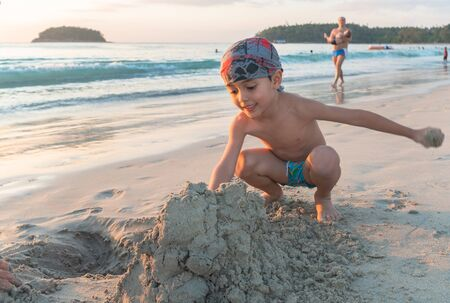 A boy wearing a turban playing in the sand on the beach during sunset at Kata beach Phuket