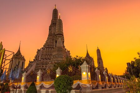 Large illuminated temple Wat Arun after sunset seen accross river Chao Phraya Bangkok, Thailand golden Buddha in side temple Wat Arun the biggest and tallest pagoda in the world
