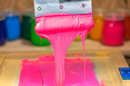 pink color dripping from hand screen printing during printing tee shirt in tee shirt factory.