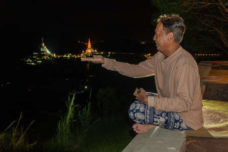 The man opened his hand so that the temple of wat Phachonkeaw was on the palm.
