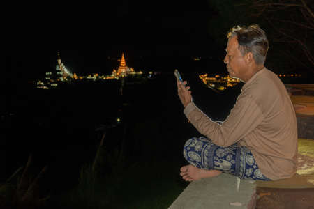 A man sitting with a mobile phone in the night.