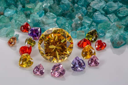 Yellow sapphire diamonds are surrounded by heart shaped diamonds on raw sky blue gemstones.jewelry in heart shape are lovely present for valentine day Stock Photo