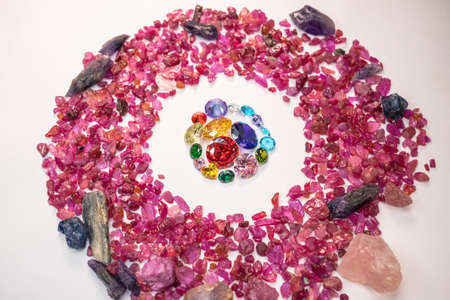 colorful diamonds in different size and many shape are place in the middle on a white ground surrounded by uncut raw red garnet stones